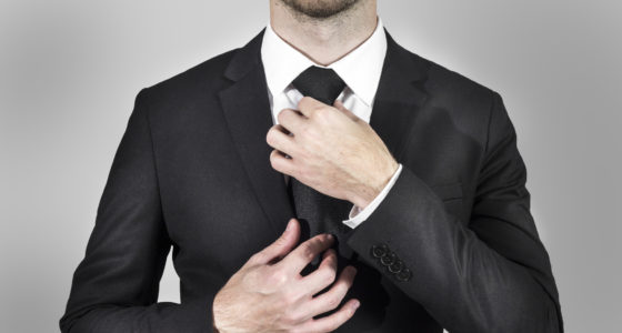 businessman in black suit correcting his necktie