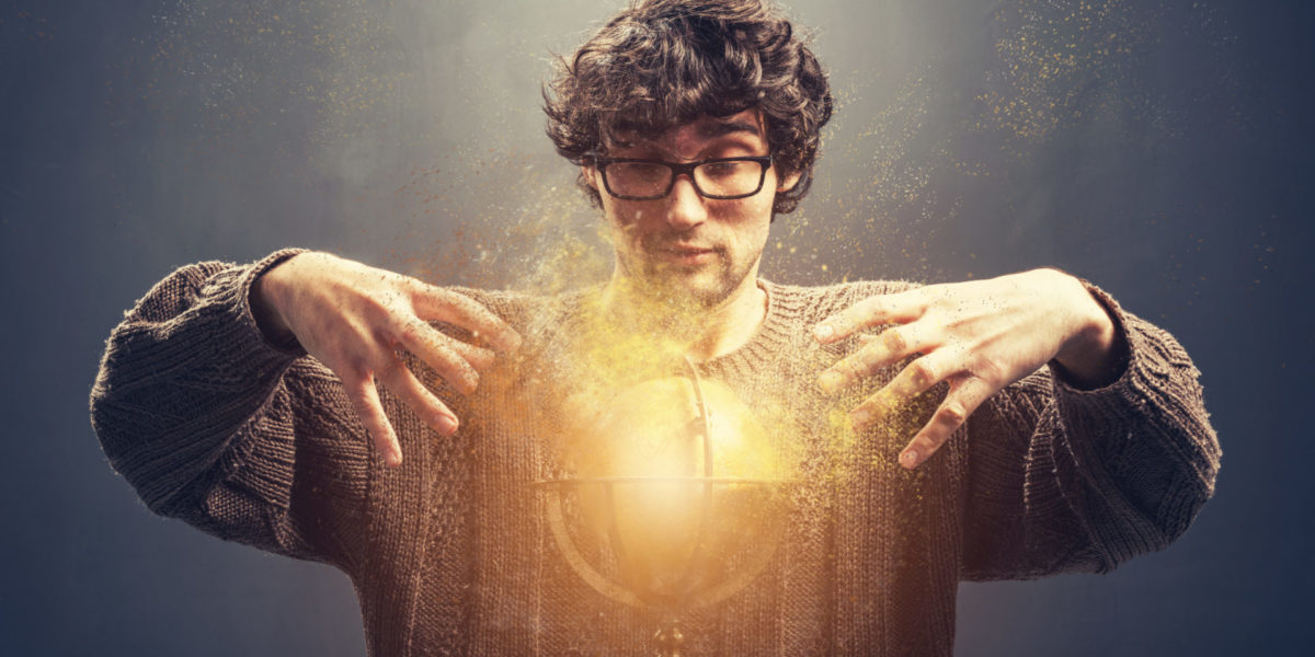 Young man gazing at the glowing crystal ball.